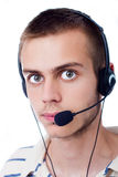 Young man talking on headset. Against a white background Royalty Free Stock Images