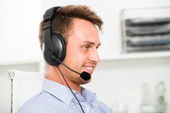 Young man talking on headset at office. Young man talking on headset at company office Royalty Free Stock Photography