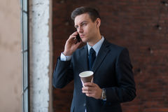 Young man talking on his mobile phone in office. Royalty Free Stock Photo