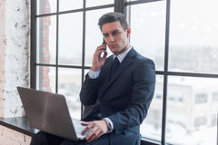 Young man talking on his mobile phone in office. Royalty Free Stock Image