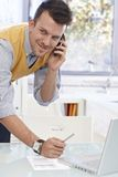 Young man talking on mobile in office, smiling Royalty Free Stock Images