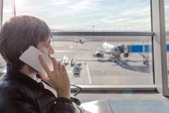 Young man talking by mobile phone in airport hall while hi is waiting for boarding plane. royalty free stock photo