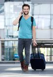 Young man talking on mobile phone with bag Stock Images