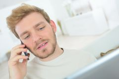 Young man talking mobile phone home. Young stock images