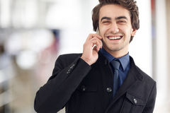 Young man talking mobile phone. In office royalty free stock images