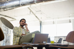 Young man talking on mobile phone in office Stock Photography
