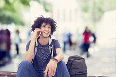 Young man talking mobile phone. Young man sitting with his backpack outdoors Stock Photography