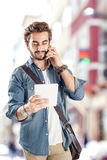 Young man talking mobile phone in street. Young handsome man talking mobile phone in street Royalty Free Stock Photos