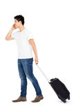 Young man talking on mobile phone while walking with suitcase Royalty Free Stock Photo