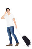Young man talking on mobile phone while walking with suitcase Stock Images