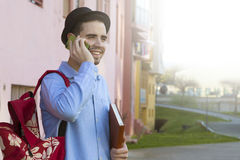 Young man talking on mobile phone. Young man of style hipster fashion talking on mobile phone royalty free stock photo