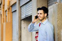 Young man talking on mobile phone. Young man of style hipster fashion talking on mobile phone royalty free stock photos