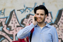 Young man talking on mobile phone. Young man of style hipster fashion talking on mobile phone royalty free stock images