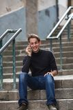 Young man talking on mobile while sitting on stone steps. Royalty Free Stock Photo