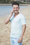 Young man talking on mobilephone at the beach Stock Image