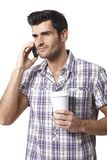 Young man talking on mobilephone drinking coffee Stock Photo