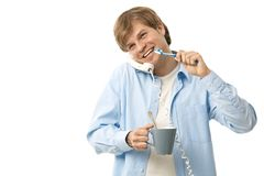 Young man talking on phone while brushing teeth. Happy man talking on phone while brushing teeth. Isolated on white stock photography