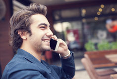Young man talking phone in cafe. Young man talking phone in the cafe Royalty Free Stock Image