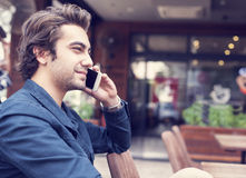 Young man talking phone in cafe. Young man talking phone in the cafe Royalty Free Stock Photo