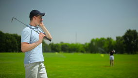 The young man talking on the phone at the course stock footage