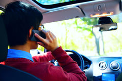 Young man talking on the phone and driving car Royalty Free Stock Photos