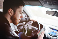 Young man talking on the phone while driving a car. A young handsome man with a beard typing a message on a smartphone. Emergency situations on the road stock photography