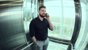 Young man talking on the phone in the elevator going up. Office worker talking on the phone in the elevator going up stock footage
