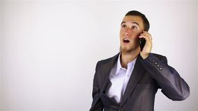 Young bearded man talking on the phone. Young man talking on the phone. grey background stock video footage