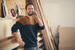 Young man talking on phone in his workshop Royalty Free Stock Photos