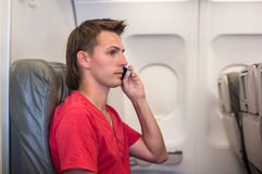 Young man talking on phone inside the aircraft Stock Images