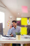 Young man talking on phone. In office Royalty Free Stock Image