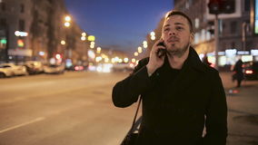 Young man talking on the phone outdoor at night in city stock footage