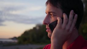 Young man talking on the phone outdoors. close-up, slowmotion, 1920x1080, hd. Young man talking on the phone outdoors stock video