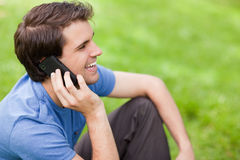 Young man talking on the phone while sitting on the grass Royalty Free Stock Images
