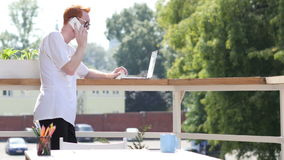Young Man Talking on Phone, Standing in Balcony Outdoor stock video footage