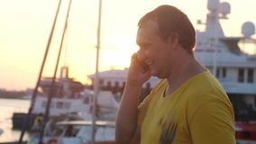 Young smiling fat man talking on mobile phone at sunset sea boats and lens flare effect. 3840x2160