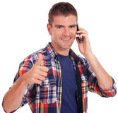 Young man talking on phone thumbs up Stock Photography