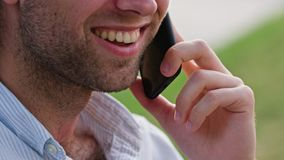 A Young Man Talking on the Phone under a Tree Stock Photo