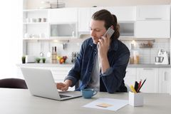 Young man talking on phone while working with laptop. At desk in home office Royalty Free Stock Photos