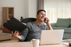 Young man talking on phone while working with laptop in home office royalty free stock image