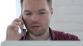 Young Man Talking on Phone while Working On Laptop stock video footage
