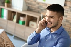 Young man talking on phone while working royalty free stock photo