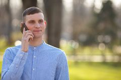 Young man talking on smart phone outdoors. Conversation, people,. Connection, cell concept Stock Photography