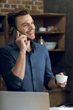 Young man talking on smartphone and holding coffee cup. Happy young man talking on smartphone and holding coffee cup Stock Photos
