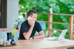 Young man talking by smartphone in outdoor cafe drinking coffee. Man using mobile smartphone. Young man with cellphone outdoors in outdoor cafe. Man using Stock Photos