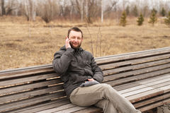 Young man talking on a smartphone outdoors Stock Photos