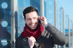 Young man talking and smiling with mobile phone outdoors Royalty Free Stock Image