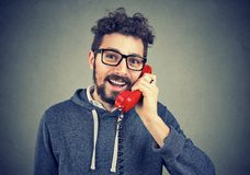 Young man talking on telephone. Young happy beard man talking on a red telephone receiving good news Stock Image