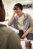 Young Man Talking To Counsellor Who Takes Notes Royalty Free Stock Photography