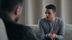 Young man talking to his therapist at therapy session
